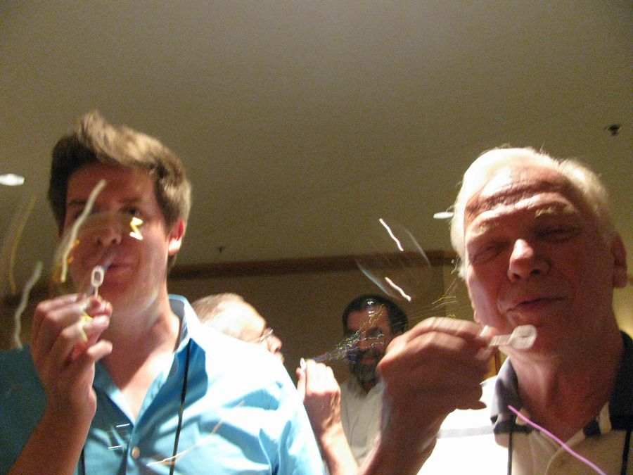 Jeremy Keene, Paul Susi (hidden) and Michael Riley blowing bubbles at the social