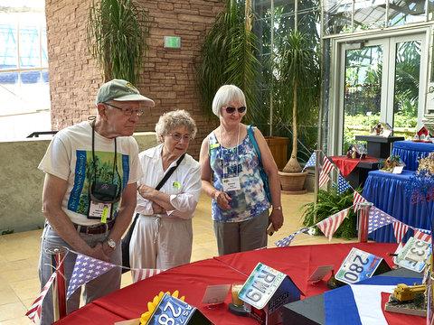 Ben Paternoster, Anne Vidaver, Bonnie Bake enjoying the display of state license plate birdhouses
